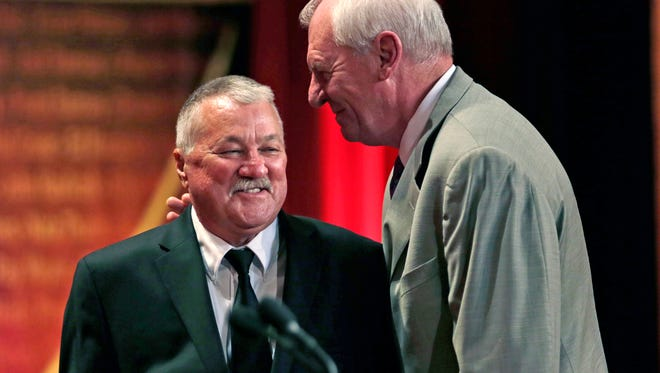 Basketball Hall of Fame inductee Louis Dampier, left, gets a pat on the back from his former college teammate Dan Issel, right, during the enshrinement ceremony for the Class of 2015 of the Naismith Memorial Basketball Hall of Fame in Springfield, Mass., Friday, Sept. 11, 2015. Dampier, a former ABA guard, played college basketball at Kentucky. (AP Photo/Charles Krupa)