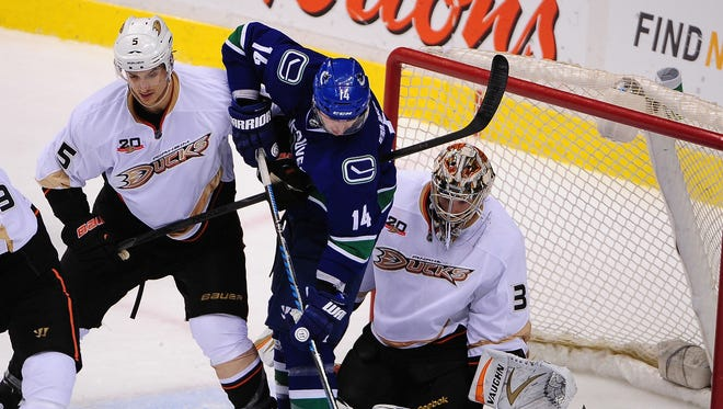 Vancouver Canucks forward Alexandre Burrows (14) moves the puck in front of Anaheim Ducks goaltender John Gibson (36) and defenseman Luca Sbisa (5) during the second period.