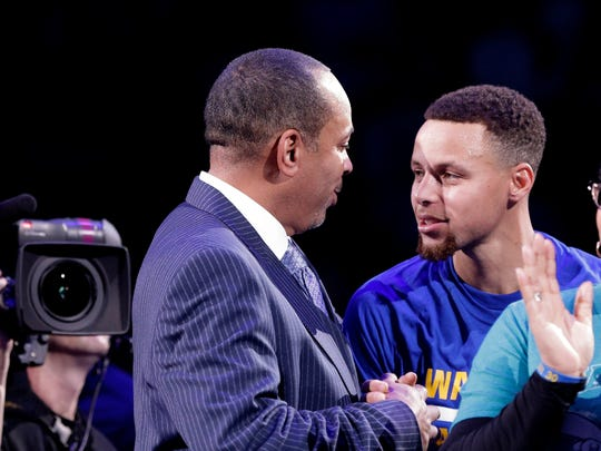 In this Dec. 2, 2015 file photo, former Charlotte Hornets Dell Curry, left, hugs his son, Golden State Warriors guard Stephen Curry, during a halftime ceremony honoring Dell Curry's career with the Charlotte Hornets at an NBA basketball game in Charlotte, N.C.