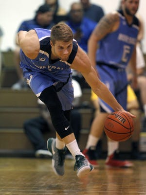 Kyle Ahrens scoops up the ball and heads up court during a Moneyball Pro-Am game, Thursday, June 29, 2017, in Dimondale.