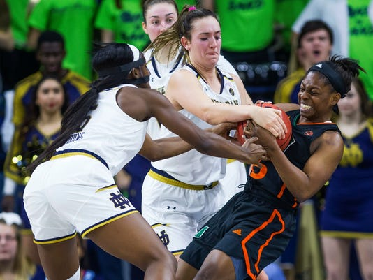 Miami's Neydja Petithomme (15) tries to rip the ball from Notre Dame's Jackie Young (5) and Marina Mabrey (3) during an NCAA college basketball game in South Bend, Ind., Thursday, Jan. 4, 2018. (Michael Caterina/South Bend Tribune via AP)