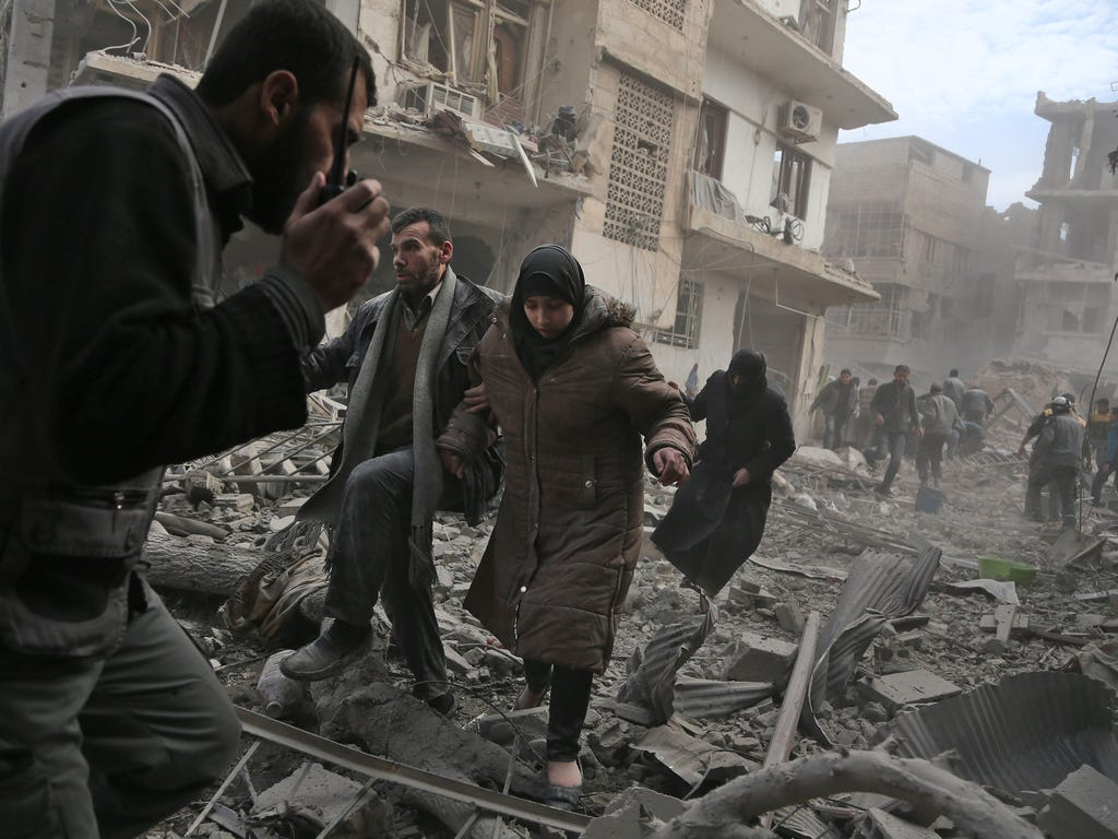 A member of the Syrian civil defense speaks on a wireless transmitter as other civilians flee from an area hit by a reported regime air strike in the rebel-held town of Saqba, in the besieged Eastern Ghouta region on the outskirts of the capital Dama