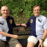 Bill Wilson (left) sits with Dave Desilvio on a bench installed in Lyon Township along the bike path to honor the coaches.