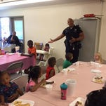 Richmond police officer Tim Davis spoke to Westwood Apartments residents during their celebration Friday.