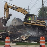 A crew sweeps up debris Wednesday after tearing down the house at 130 N. Sixth St. in Richmond.