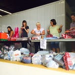 Volunteers and FLORIDA TODAY employees wrap gifts for seniors receiving presents through the Reaching Out Holiday Fund.