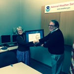 Alana Hastings accepts the Dick Hagemeyer Award from Don Britton, meteorologist-in-charge at the National Weather Service in Great Falls, on behalf of her husband, Hugh Hastings Jr., who died in 2013. The award is granted to a weather observer for 45 years of service.