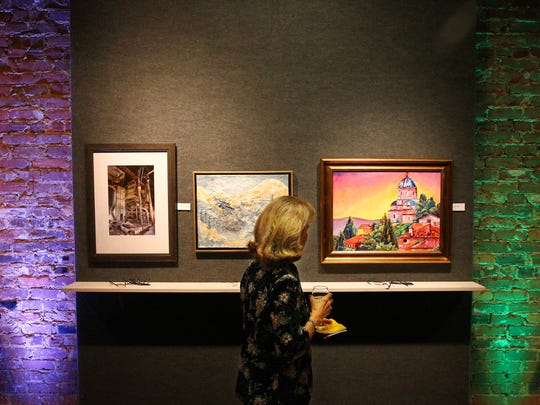 Mary Ellen Ellenburg walks past a group of paintings