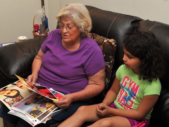 Sandy Cadena and her granddaughter Bella look at pictures