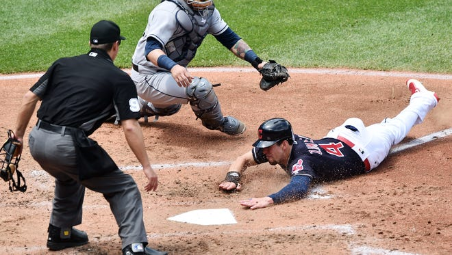 Cleveland Indians center fielder Bradley Zimmer (4) scores as Tampa Bay Rays catcher Jesus Sucre (45) is late with the tag during the third inning at Progressive Field.