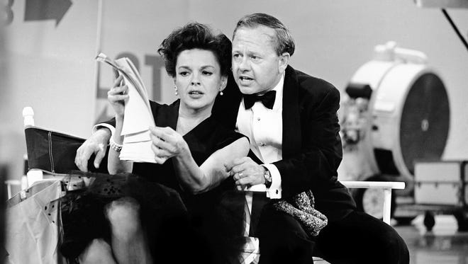 Judy Garland and Mickey Rooney put their heads together over a television script for their first onstage reunion in 18 years, for the taping of the first of 32 variety shows which Garland will do for CBS next season on June 26, 1963.