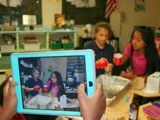 A fourth grade student captures video of Emily Ybarra