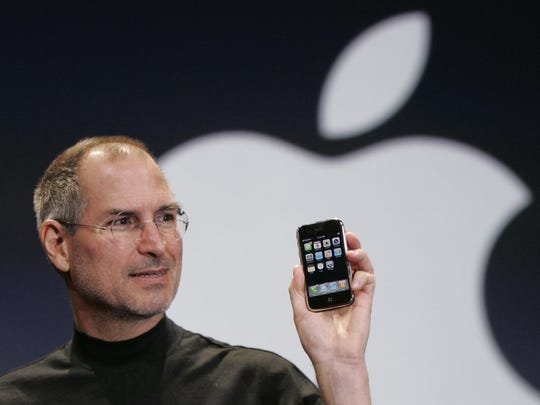 Apple CEO Steve Jobs holds up an Apple iPhone at the