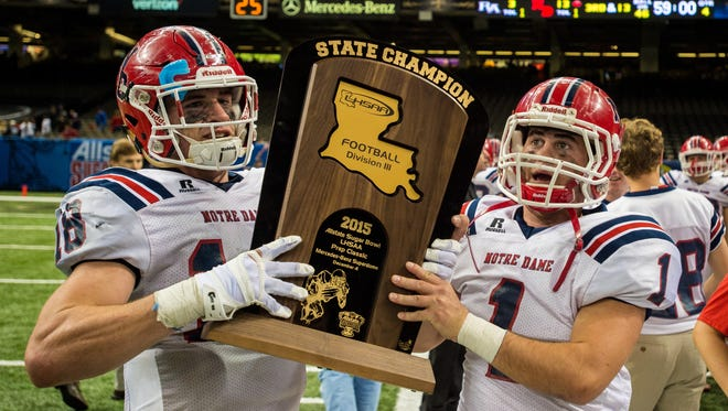 Members of the Notre Dame Pioneers football team hold the Division III state championship trophy after beating Riverside Academy 13-3 in the Mercedes-Benz Superdome.