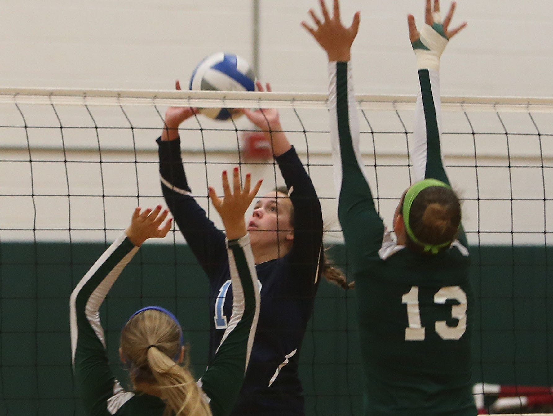 Westlake's Laine Peterson (13) puts a shot over Pleasantville's Chloe Violette (5) and Brianna Tucci (13) during volleyball action at Pleasantville High School Sept. 30, 2015.