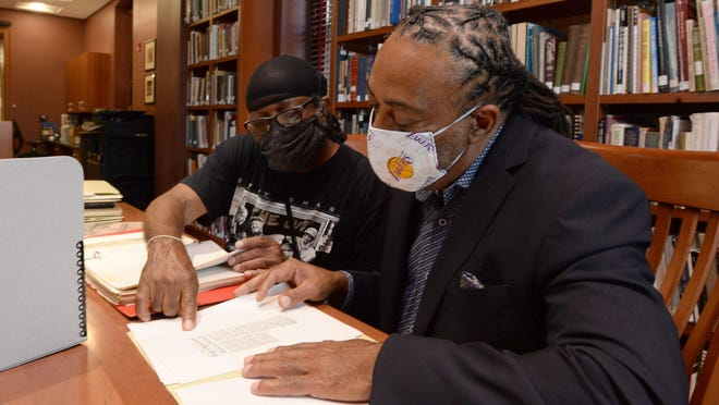 Gary Horton, left, president of the NAACP's Erie chapter, and his brother Andre Horton, Erie County Council member, look over a collection of civil rights material collected by their father Howard Horton. The collection is housed at the Hagen History Center in Erie.