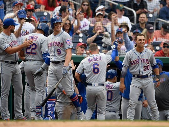 New York Mets' Jeff McNeil (6) celebrates with the dugout after he scored on a single by J.D. Davis during the eighth inning of a baseball game against the Washington Nationals, Saturday, March 30, 2019, in Washington. The Mets won 11-8. (AP Photo/Nick Wass)