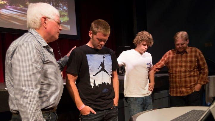 Church elder Michael McGregor (left) prays for Tyler