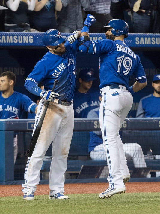 Toronto Blue Jays' Jose Bautista, right, is greeted by Steve Pearce after hitting a two-run home run against the Seattle Mariners during the third inning of a baseball game in Toronto on Friday May 12, 2017. (Fred Thornhill/The Canadian Press via AP)