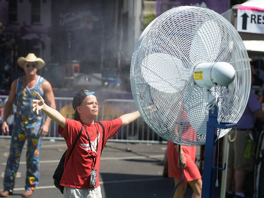 Ryder Powell,10, uses a misting fan to cool down during