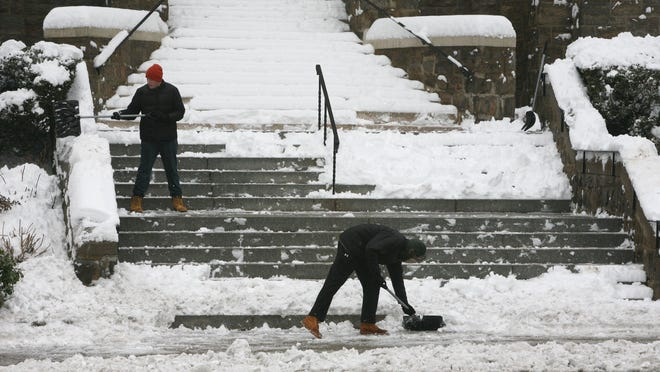 Christopher Fulham and Ciaran Burke, workers at St. John the Baptist Church on Yonkers Avenue in Yonkers, clear the stairs of snow Saturday.