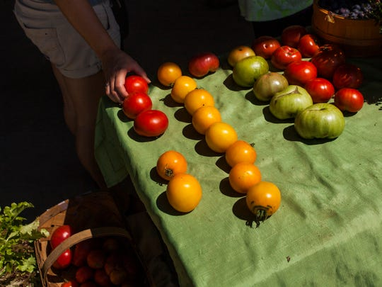 A customer picks out tomatoes from a Waynesboro Farmers