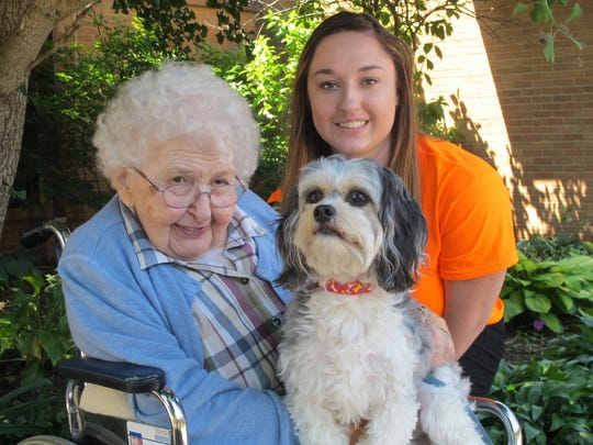 Resident Virginia Roth and social services assistant Katilin Miller pose for a photo with Luke outside Pleasantview Home Retirement Community in Kalona.