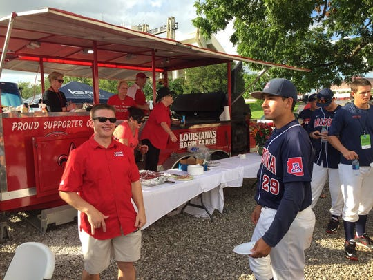 "Arizona baseball players are treated to food by tailgating Ragin' Cajuns fans on Sunday at the NCAA Lafayette Regional at M.L. ""Tigue"" Moore Field."