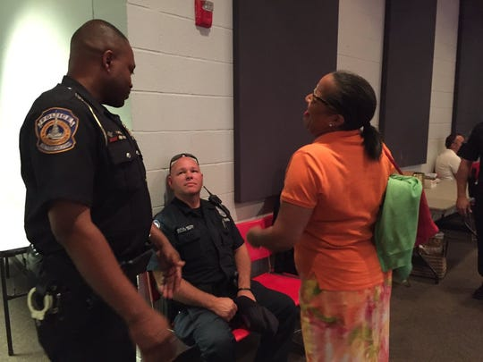 Indianapolis police officers meet with an Indianapolis resident at the prayer vigil on Saturday at Light of the World church in Indianapolis.