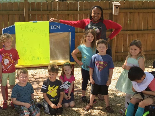 "The ""Yellow Room Kids"" at the Ann Campbell Early Learning Center at MTSU pose for a photo with their lemonade-stand sign in the Fairview Building playground."