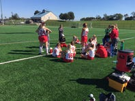 Annville-Cleona field hockey coach Sue Felty (kneeling) encourages her team during halftime of Saturday's Lancaster-Lebanon League playoff game against Warwick. A-C lost by a 4-0 score but gave a good account of itself in the setback.