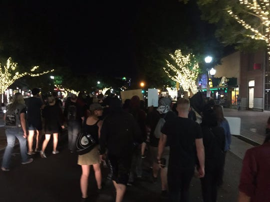 """People protesting President-elect Donald Trump walk down Mill Avenue in Tempe on Nov. 11, 2016. """"One-two-three-four, one solution, civil war,"""" some chanted."""