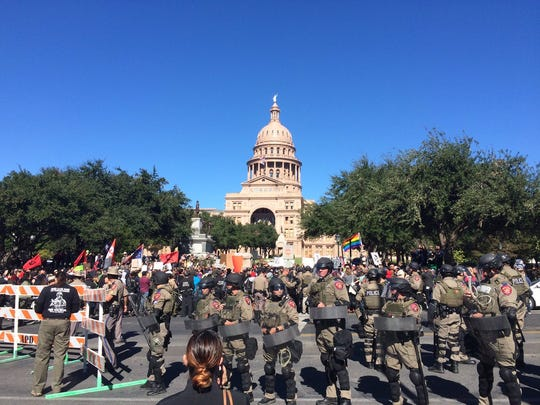 Troopers in riot gear attempt to keep order at a racially charged demonstration Saturday, Nov. 19, 2016, at the Texas Capitol. The protests followed the unveiling of a monument to  African-American history on the Capitol's south lawn.