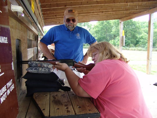 Bill Balda, hunter education supervisor for the Kentucky Department of Fish and Wildlife Resources, instructs Tia Edwards, information specialist for Kentucky Fish and Wildlife, on proper rifle shooting techniques at the Kleber Wildlife Management Area rifle range in Owen County.
