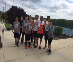 Palmyra freshman Ben Clary, third from right in orange shirt, celebrates with his Cougar tennis teammates after capturing the Mid-Penn AAA singles title on Monday.