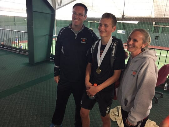 Palmyra's Ben Clary with his coaches, Keith and Abbie Mahaffey, after winning his third place match to qualify for states