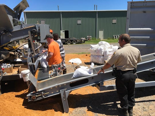 Sandbags are loaded into a container to be ready for future flooding events.