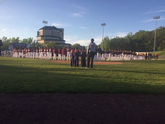 The baseball teams from Verona (left) and Cedar Grove (right) stand for the National Anthem.