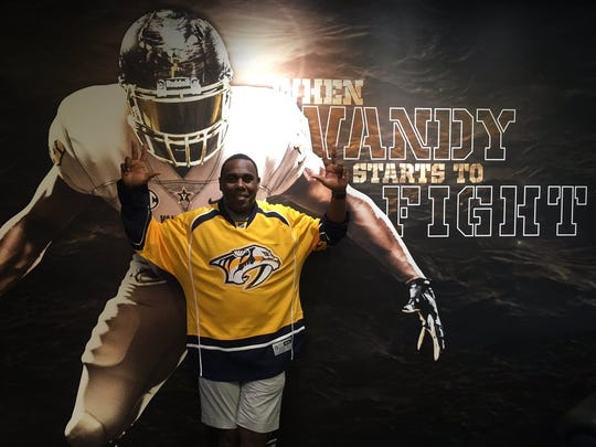Vanderbilt football coach Derek Mason poses with a Predators jersey