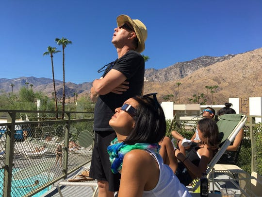 People watch the Great American Eclipse on the balcony of Ace Hotel & Swim Club in Palm Springs on Aug. 21, 2017.