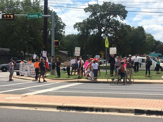 Protesters wait to greet President Donald Trump's motorcade