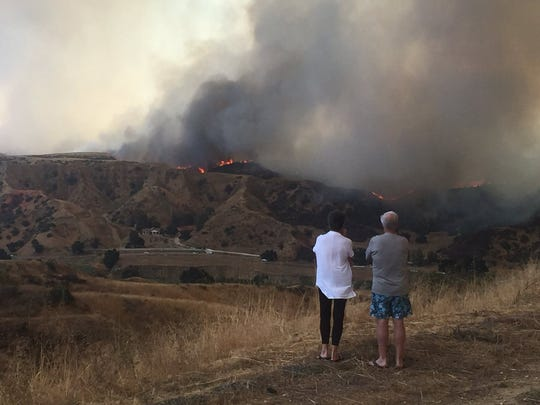People in Redlands look at the Palmer fire as it began