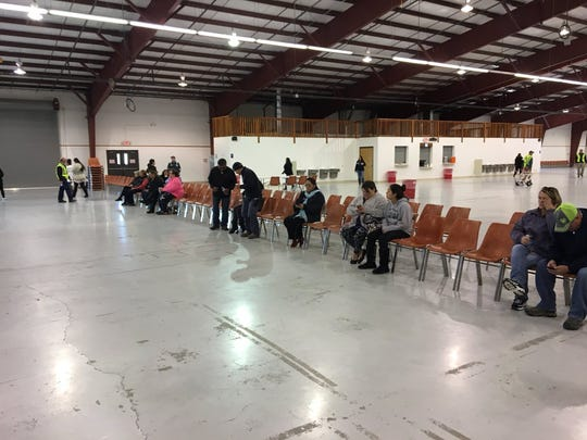 Families of Aztec High School students wait to pick up their children at the McGee Park Convention Center Thursday after a fatal shooting at the school.