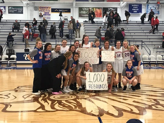 Whiteland's girls basketball team celebrate Mackenzie Blazek's 1,000th career rebound. Blazek is back row center holding a sign.