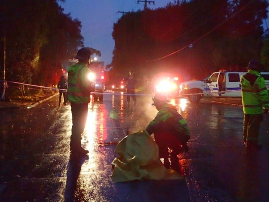 Santa Barbara County Fire Department firefighters assist a woman who was pulled from a debris pile in Montecito.