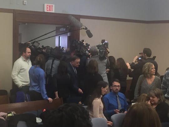 A media crowd surrounds Michigan State University President Lou Anna Simon on Jan. 17, 2018 in the back of the courtroom where Larry Nassar's sentencing hearing is taking place.