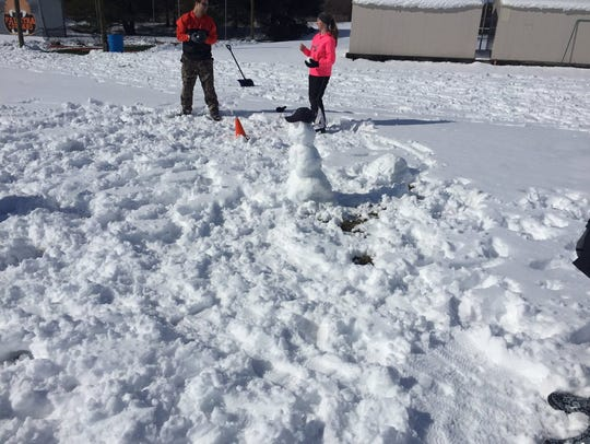 A snowman, with a baseball hat, keeps a watchful eye