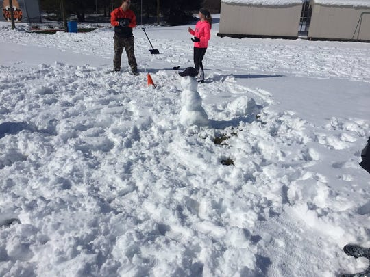A snowman, with a baseball hat, keeps a watchful eye on Palmyra softball practice.