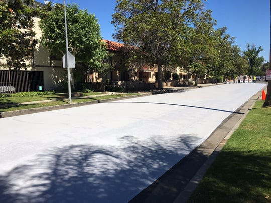 """City street crews applied a """"cool pavement"""" treatment on Jordan Avenue in the Canoga Park neighborhood of west Los Angeles. The treatment is meant to lower temperatures in the area."""