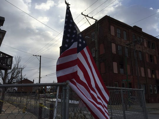 An American flag is placed at the Weaver building, where two York firefighters died Thursday in a collapse, following a fire there.